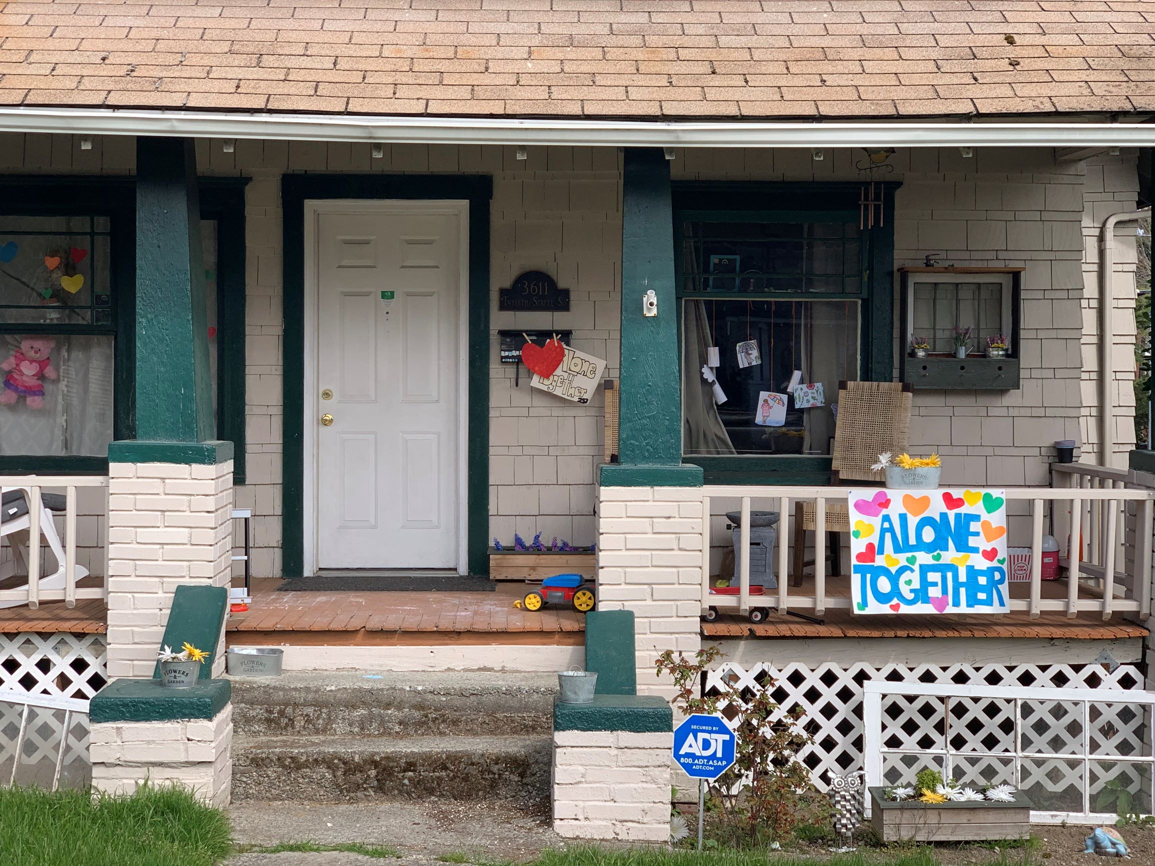 """A house in central Tacoma with several handdrawn signs including a large """"Alone Together"""""""